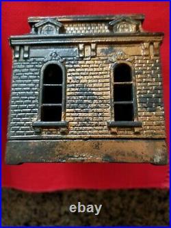 Cast Iron Still Home Bank WithMan standing At Door